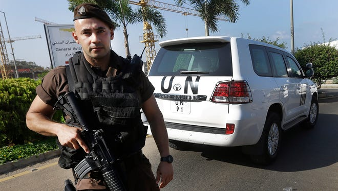 A Lebanese special forces policeman escorts the vehicles of U.N. experts on the arrival at the private jet terminal, at Beirut international airport in Lebanon on Saturday.