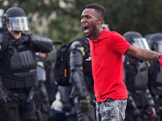 A protester yells at police in front of the Baton Rouge Police Department headquarters after police arrived in riot gear to clear protesters from the street in Baton Rouge, La., Saturday, July 9, 2016. Several protesters were arrested. (AP Photo/Max Becherer)