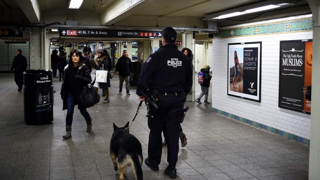 A New York Police Department (NYPD) officer patrols with his dog in a subway station on March 22, 2016, in New York. New York and Washington stepped up security in the wake of the attacks in Brussels on March 22, deploying counter-terrorism reinforcements and the National Guard to airports and stations, officials said. The New York Police Department (NYPD) said there was no indication that the attacks in Belgium were connected to New York, but ordered the steps as America's biggest city of 8.4 million began the morning commute. Around 35 people were killed and more than 200 wounded on Tuesday in bombings at the Brussels airport and a metro station in the city that is home to the European Union and NATO. / AFP PHOTO / Jewel SAMADJEWEL SAMAD/AFP/Getty Images