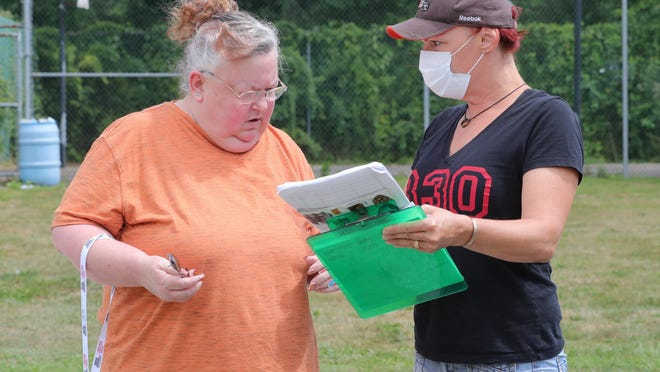 Kimberly Trenary, left, and Kristi Evans seek signatures to recall Barberton Mayor William Judge on Aug. 23, 2020, in Barberton, Ohio.