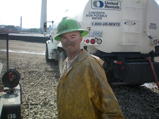 Workers were told coal ash was safe, a lawsuit alleges. This smiling worker was up to his eyeballs in it.