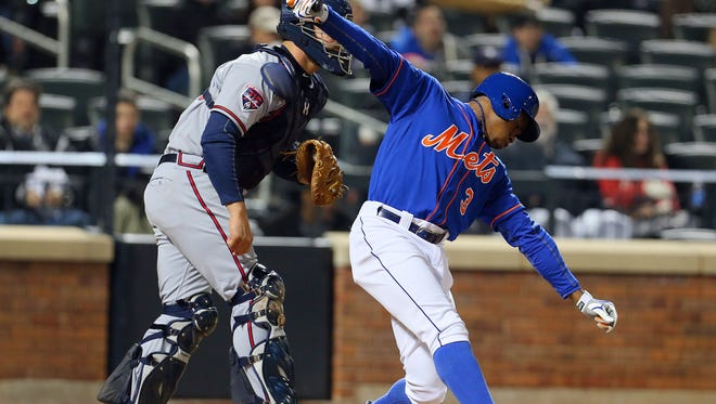 The Mets' Curtis Granderson reacts to striking out to end the eighth inning in front of Atlanta Braves catcher Evan Gattis.
