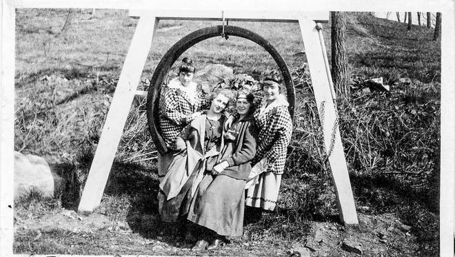 The Daniels twins, Clara Anderson and a friend sitting on the fire bell across from Heaton's barn in a Sundvik family photo.