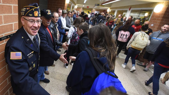 Retired Air Force Master Sgt. David Copenheaver shakes hands during a big greeting Friday morning before a Veterans Day program at Red Lion Area Junior High.