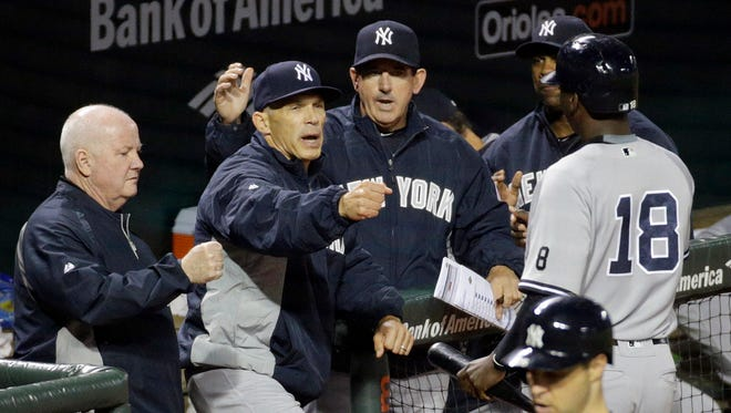 New York Yankees manager Joe Girardi, second from left, greets Didi Gregorius (18) after he scored when teammate Brett Gardner was hit by a pitch with the bases loaded in the eighth inning of a baseball game against the Baltimore Orioles in Baltimore, Wednesday, May 4, 2016.
