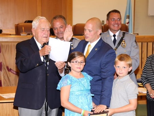 Toms River's newest police officer, William Resetar, is sworn in by Mayor Thomas F. Kelaher July 25.