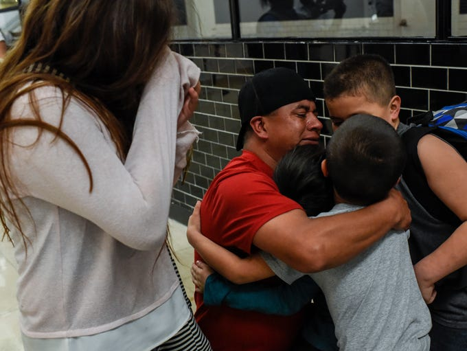 Antonio Cuahua (second from left) embraces his children,