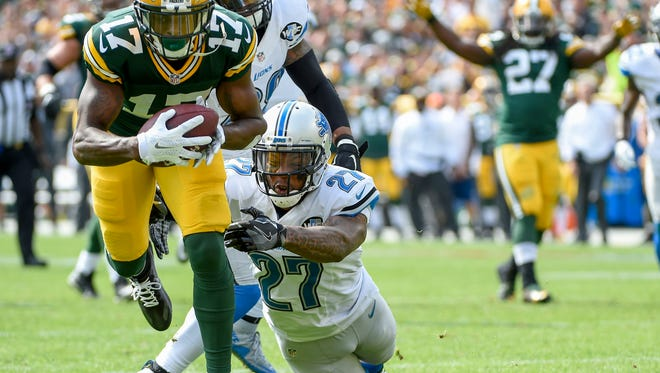 Packers wide receiver Davante Adams (17) breaks a tackle by Lions safety Glover Quin (27) after catching a pass to score a touchdown in the first quarter Sunday in Green Bay, Wis.