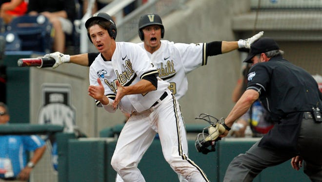 Vanderbilt Commodores runner Bryan Reynolds (20) and right fielder Rhett Wiseman (8) celebrate Reynolds's run against the UC Irvine Anteaters during game six of the 2014 College World Series at TD Ameritrade Park Omaha.
