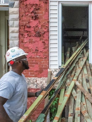 Working for the Humanim company Details, Damon Toogood stacks planks of flooring outside an abandoned East Baltimore row home.