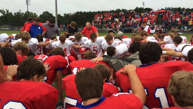 Copiah Academy and Jackson Prep players pray for their fallen teammates before Saturday's game.