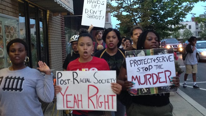 Protesters march on Thursday in Highland Park in solidarity with residents of Ferguson, Mo., who rose against the police shooting of an unarmed black man.