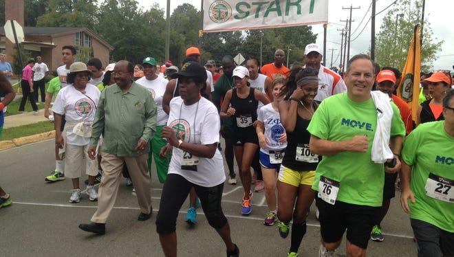 FAMU's 11th president Elmira Mangum leads the pack at the start of the 5K Walk/Run/Roll/Stroll at Bragg Memorial Stadium.