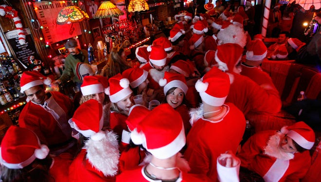 "New York, NY Hundreds of ""Santas"" get together in NYC for ""SantaCon"". They dress like Santa and are directed to a bar (Rudy's Bar in Hell's Kitchen, here, ) for a short time, then travel to another bar."