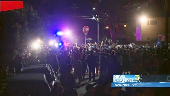This video image provided by KEYT-TV shows a crowd confronting police at a disturbance Saturday April 5, 2014, during a weekend college party in Southern California that devolved into a street brawl. About 100 people were arrested and at least 44 people were taken to the hospital.