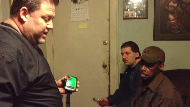 Curtis Jones (right), a resident of Hotel Somerset, sits in a room he says is haunted. Robert McCaffrey (left) and Jon McCaffrey of East Brunswick, N.J.-based Paranormal Diagnostics Group are investigating.