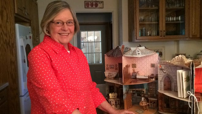 Beverly Stimac of Biron has a collection of about 100 pop-up books, from simple to extravagant. Her she stands in her kitchen with  pop-up castle and doll house books.