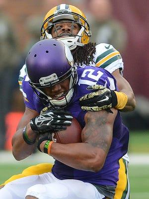 Green Bay Packers cornerback Tramon Williams (38) tackles receiver Charles Johnson (12) against the Minnesota Vikings at TCF Bank Stadium November 23, 2014.