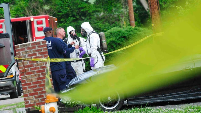 Fire and police work in hazmat suits at a house fire, where two people were injured on Clovernook Drive in Nashville Tenn. May 27, 2014.