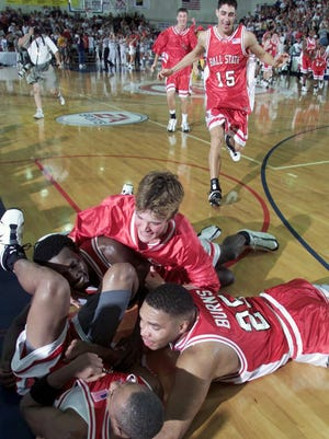 Ball State's Patrick Jackson (bottom center) is mobbed by teammates including Brian Burns (right), Theron Smith (top left), and Scott Bushong (top right) as the buzzer sounded and Ball State defeated Kansas 93-91 in this Nov. 19, 2001, photo.