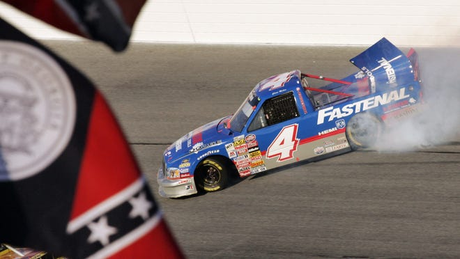 Chase Miller slides his Dodge past an old Georgia flag and a Confederate stars on bars flag during running of a NASCAR Truck series auto race at Atlanta Motor Speedway in Hampton, Ga., in 2006. NASCAR has a checkered racial history, from a long-time affinity for Confederate flags among the fan base to a driver losing his job just this season for casually uttering a racial epitaph.