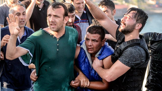 A Turkish soldier who participated in the attempted coup, center in blue, is apprehended by other men on Istanbul's Bosporus Bridge on July 16, 2016.