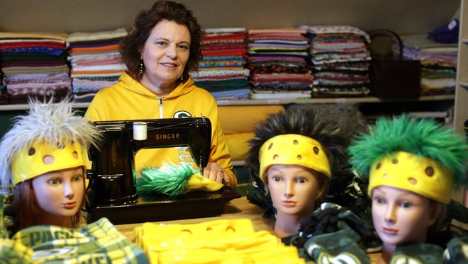 Ann Fruzen's upstairs studio in her town of Glenmore home is filled with fabric and thread for the Packers scarves, mittens, hats and, her newest creation, headbands with hair she makes.