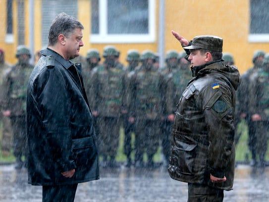 A Ukrainian soldier salutes President Petro Poroshenko