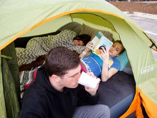 Connor McMahon, left, Ari Pearlman, right, and Ilana Schwartz hang out in their tent as they wait for the Chick-fil-A opening, Wednesday, March 29, 2017, in Okemos, Mich.