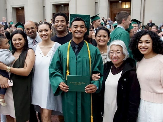 Jeffrey Brown is surrounded by his family at his graduation