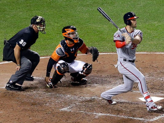 Washington Nationals' Bryce Harper, right, watches his solo home run in front of Baltimore Orioles catcher Caleb Joseph, center, and home plate umpire Paul Nauert in the sixth inning of an interleague baseball game, Saturday, July 11, 2015, in Baltimore. (AP Photo/Patrick Semansky)