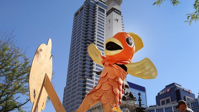 """Monument Circle will soon be more of a place to relax, socialize, play game and collaborate with many local artists as part of """"Spark: Monument Circle"""" which launches Aug. 1 and will feature daily activities for 11 weeks. Here """"The Big Carp"""", mascot of """"Spark: Monument Circle"""", dances and waves to pedestrians on the Circle."""