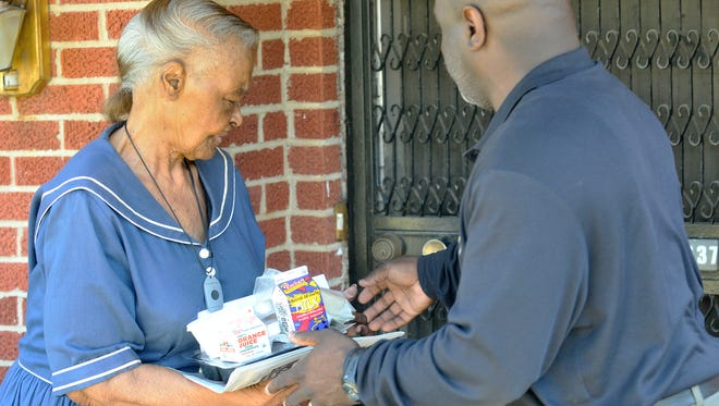 Annie Nichols meets Meals on Wheels volunteer Kerwin Washington at her door as Washington delivers food, newspapers and other items on his route in Montgomery on Tuesday, March 17, 2015. The Montgomery Area Council on Aging is participating in the 13th annual National March for Meals.
