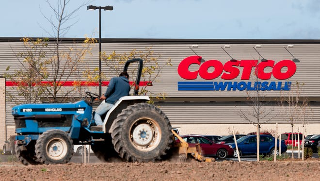 Landscapers work to get fresh sod down before the grand opening of the Costco in Bellevue on Oct. 14, 2013. Two outlots fronting Costco on County GV/Monroe Road were recently bought for development.