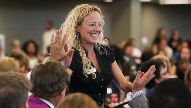 F&M Bank Assistant Vice President of Business Development Stacey Streetman receives high fives as she accepts the award for F&M Bank being named the Reader Choice Award 2016 Best Bank winner on Thursday.