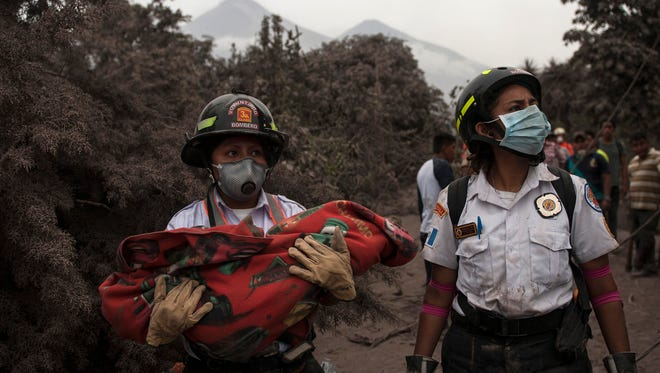 "A firefighter carries the body of a child recovered near the Volcan de Fuego, or ""Volcano of Fire,"" in Escuintla, Guatemala, Monday, June 4, 2018."