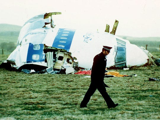 A police officer walks by the nose of Pan Am flight 103 in a field near the town of Lockerbie, Scotland where it lay after a bomb aboard exploded, killing a total of 270 people, in this December 21, 1988.
