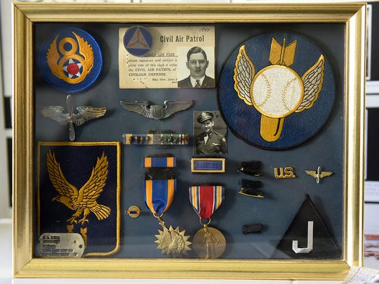 Don Fish, 100, shows some memorabilia from his time as a B-17 bomber co-pilot flying missions over Germany Thursday, Oct. 19, at Country Manor in Sartell.