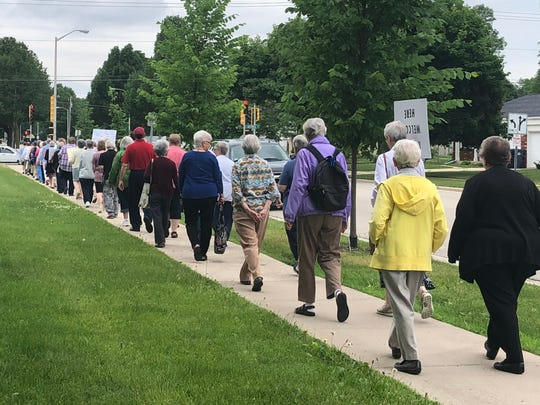 Religious sisters and other community members march silently around Marian University's campus Wednesday afternoon to protest immigration policies that separate families.