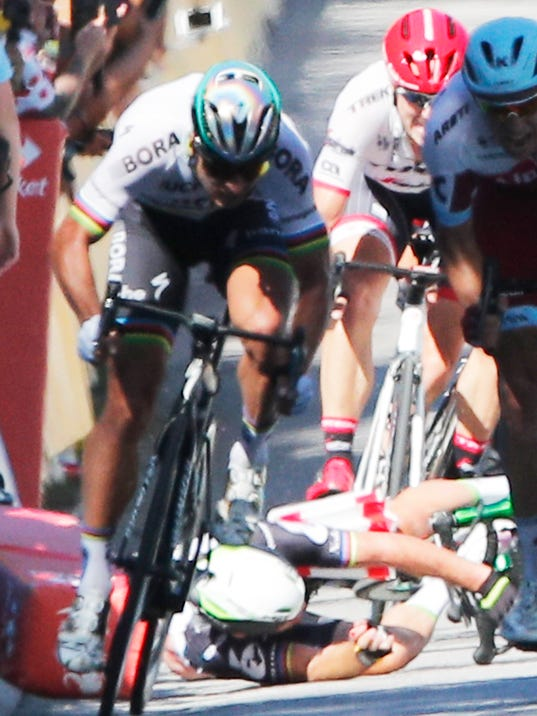 Peter Sagan of Slovakia, left, sprints as Britain's Mark Cavendish, crashes, during the sprint of the fourth stage of the Tour de France cycling race over 207.5 kilometers (129 miles) with start in Mondorf-les-Bains, Luxembourg, and finish in Vittel, France, Tuesday, July 4, 2017. World champion Peter Sagan has been disqualified from the Tour de France for causing a crash in a chaotic sprint finish that left Mark Cavendish needing treatment for his injuries and further examinations in a hospital. (AP Photo/Christophe Ena)