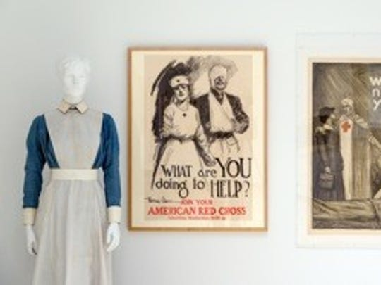 """From left, a Liberty of London VAD (Voluntary Aid Detachment) ward uniform, British Expeditionary Force; and Red Cross recruiting posters as part of """"The War to End All Wars: Artists and World War I"""" at the Herbert F. Johnson Museum of Art."""