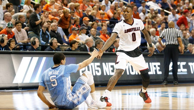 Louisville's Terry Rozier helps UNC's Marcus Paige up after the two collided in the final seconds of the game. Mar. 12, 2015