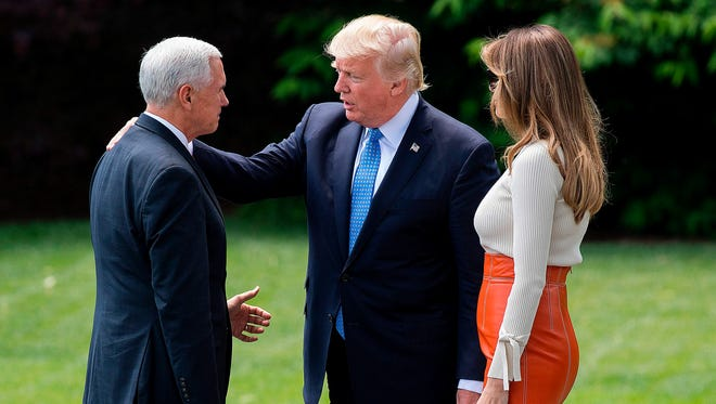 President Donald Trump and First Lady Melania Trump speak with Vice President Mike Pence as they leave the White House in Washington, DC, May 19, 2017.