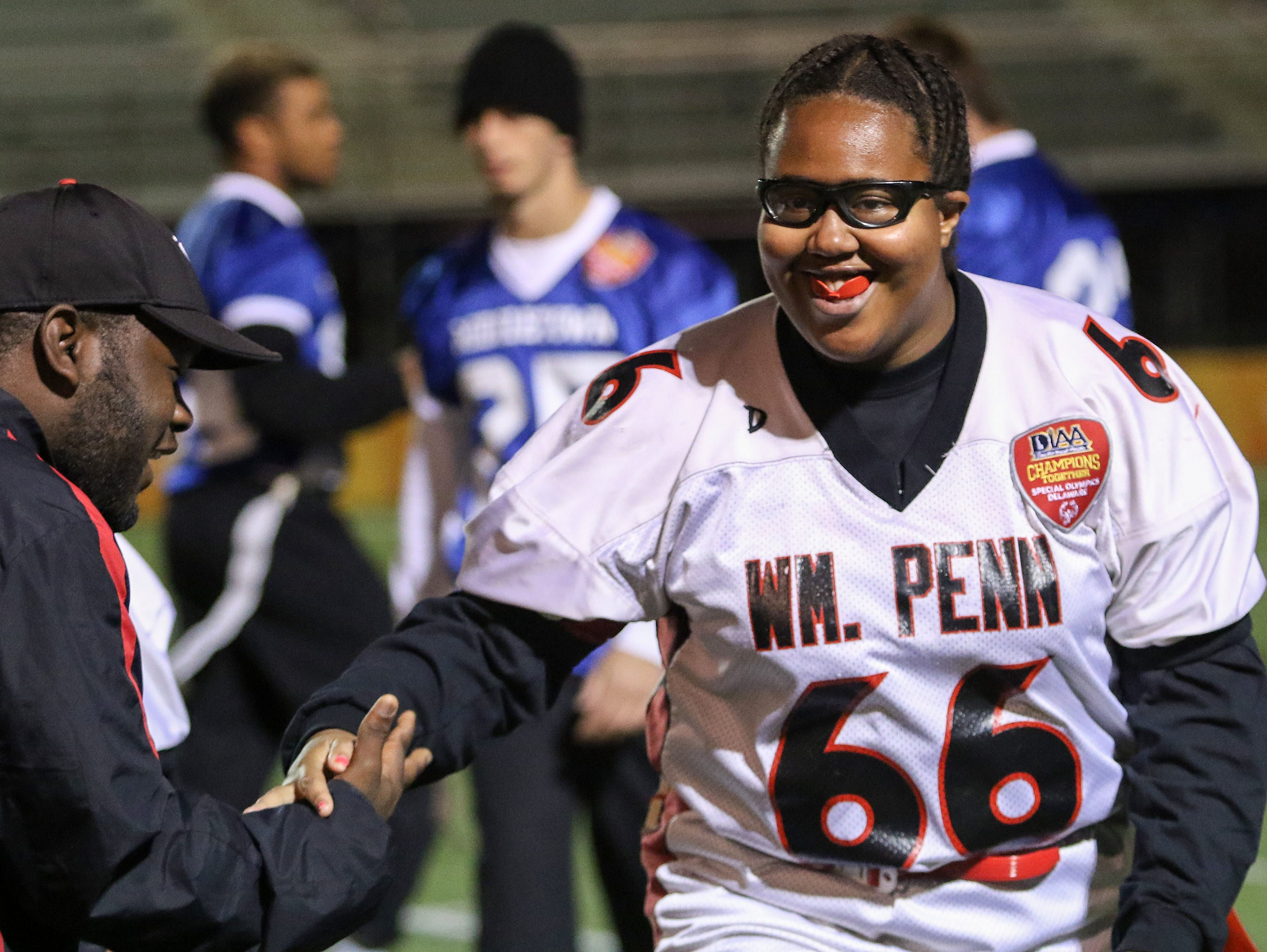 Danielle Alphonse, of the William Penn Unified Football team, gets a five from assistant coach Terrence Walker after she scored a touchdown during a DIAA Unified Football game.