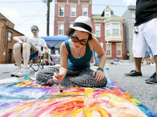 Faith Reisinger of Carlisle works on a painting for The Parliament Arts Organization during Equality Fest Sunday, Aug. 2, 2015. The second annual Equality Fest, held in the 100 block of East King Street in York, featured a vow renewal ceremony and a wedding expo in the Bond Building, as well as music, crafts, food and games. The festival, which was inspired last year by the legalization of gay marriage in Pennsylvania, is designed to celebrate the diversity of Pennsylvania and York residents.