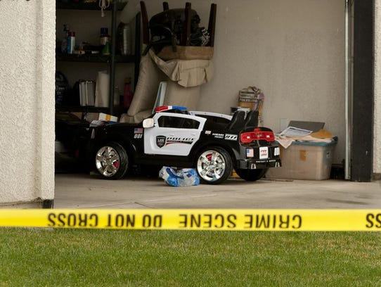 A toy police car sits in the garage as Tulare County
