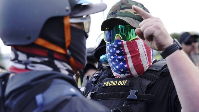 """FILE - In this Sept. 26, 2020 file photo, a right-wing demonstrator gestures toward a counter protester as members of the Proud Boys and other right-wing demonstrators rally in Portland, Ore. President Donald Trump didn't condemn white supremacist groups and their role in violence in some American cities this summer. Instead, he said the violence is a """"left-wing"""" problem and he told one far-right extremist group to """"stand back and stand by.†His comments Tuesday night were in response to debate moderator Chris Wallace asking if he would condemn white supremacists and militia groups. Trump's exchange with Democrat Joe Biden left the extremist group Proud Boys celebrating what some of its members saw as tacit approval."""