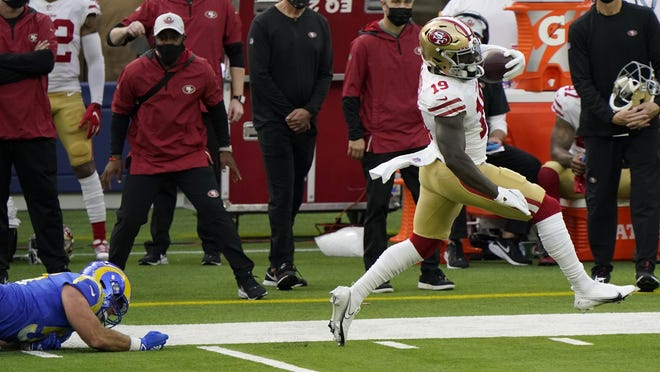 San Francisco 49ers wide receiver Deebo Samuel gets past Los Angeles Rams linebacker Troy Reeder after catching a pass during the first half of Sunday's game. If he's available in your league this late in the season, he's a must-get.