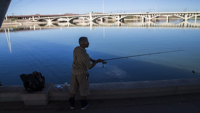 Jesse Aponte fishes for some bass under the bridge at Tempe Town Lake on Nov. 7, 2016.
