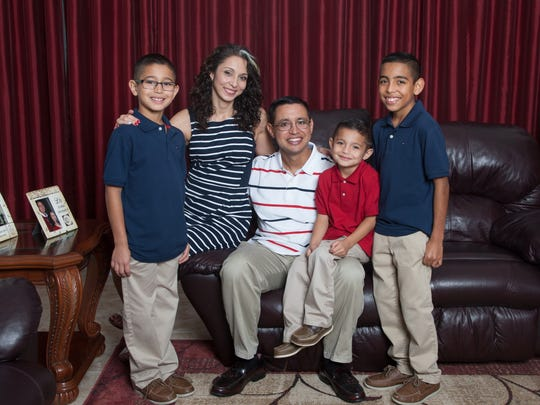Portrait of the Barnhart family (l-r) Xavier, 8,  Michele, Bernardo, Benito, 5, and Bernardo Jr, 10, at their home in Ave Maria, FL on Tuesday, December 22, 2015.  Bernardo is being honored for a volunteer award to his native Immokalee. He has been cancer free for more than 17 years. When he was going through treatments, he was told he'd have no children. Photo by Gregg Pachkowski